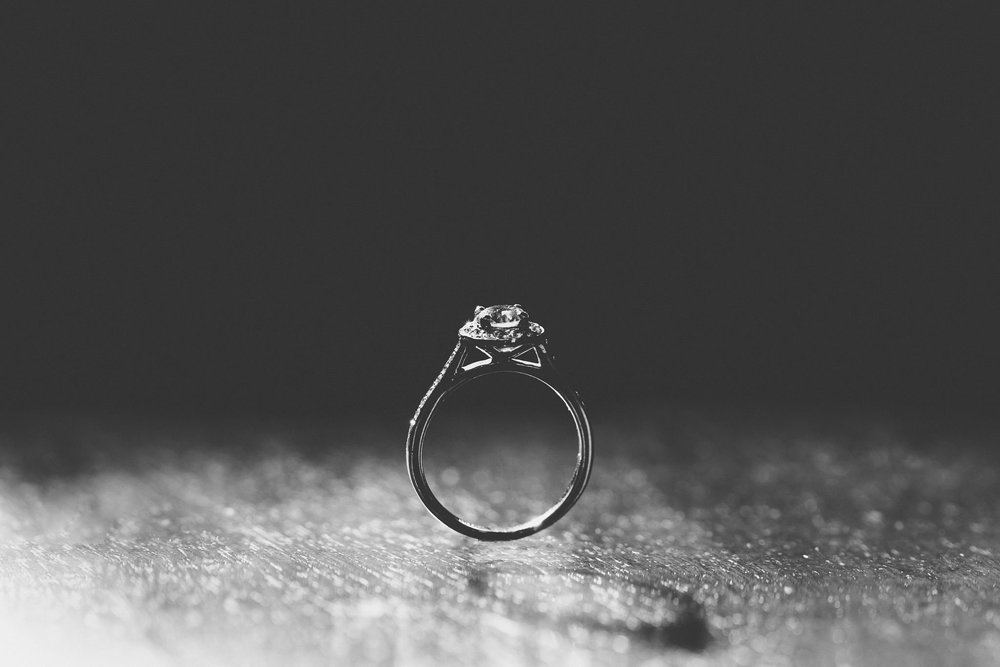 The bride's engagement ring performing a balancing act while being backlit by window light at the Welcombe Hotel, Stratford.