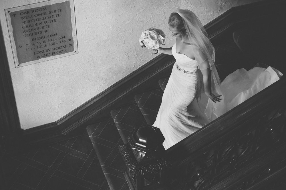 The bride elegantly walks down the staircase at the Welcombe in Stratford to her wedding ceremony. I love the black and white treatment.