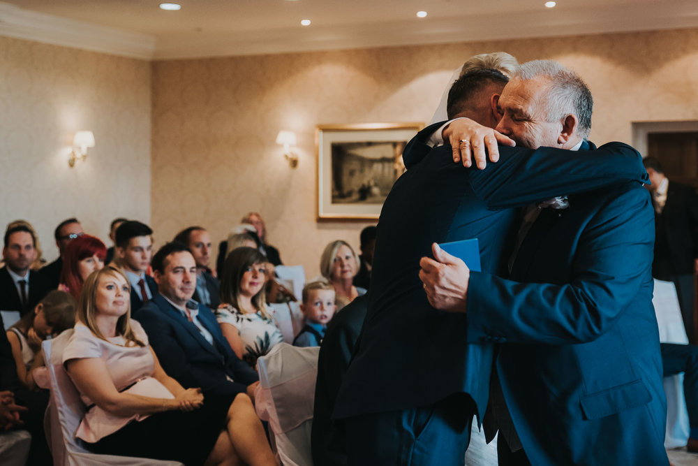 The groom and his father share a moment and a warm hug during the ceremony.