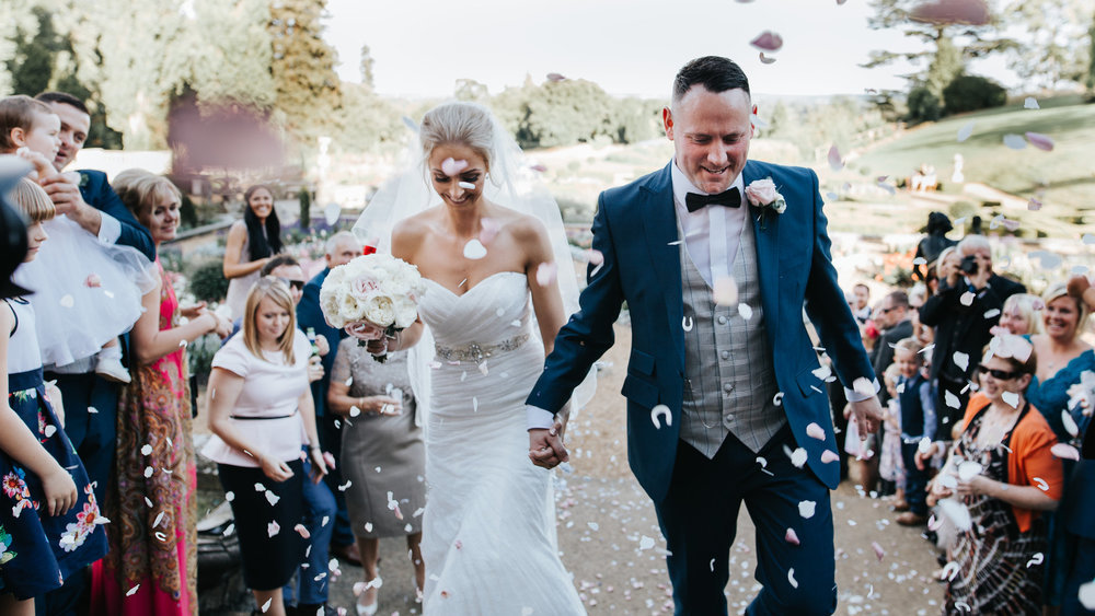 The bride and groom happily make their way through their guests and colourful confetti on their wedding day at the Welcombe in Stratford.