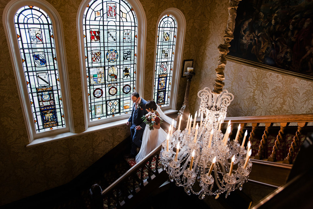 Bride and her father making their way down the grand staircase, past the beautiful stained glass windows and elegant chandelier at Kilworth House in Leicester.