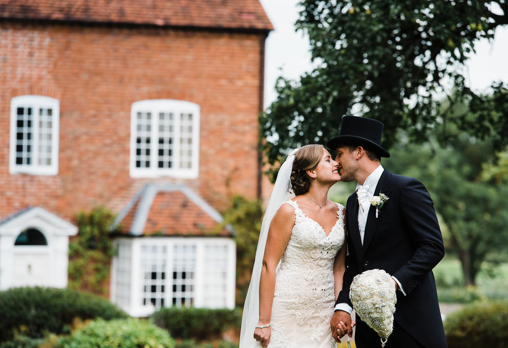 Romantic and stylish couple share a kiss during their summer wedding day at Wethele Manor. The groom looks very cool in his top hat and tails.