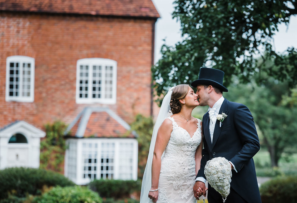 Bride and groom sneak a kiss at their summer wedding at Wethele Manor in Coventry.
