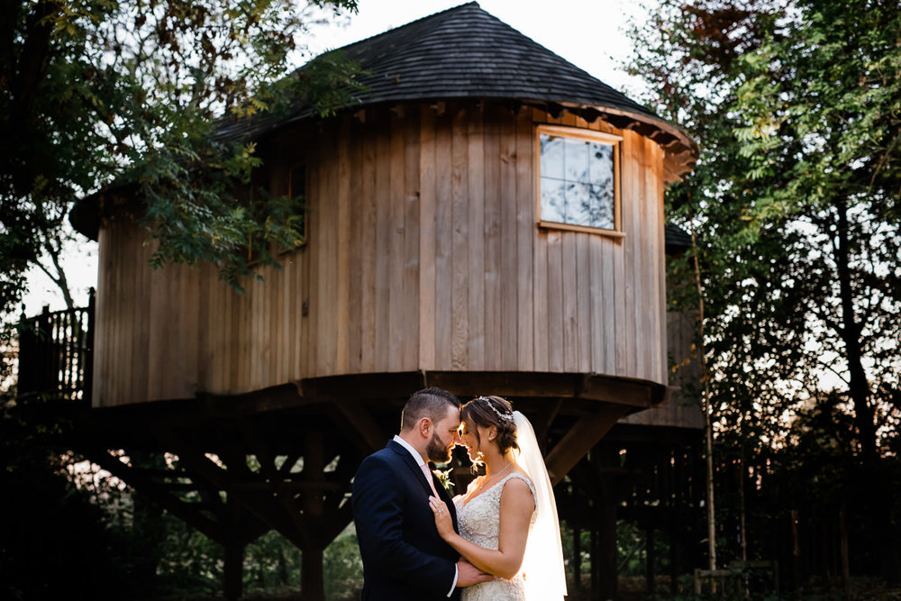 romantic wedding photo in west midlands. bride and groom cuddle in front of tree house. Groom wore a dark blue suit with a blush pink tie and bride with a sweet heart neckline.