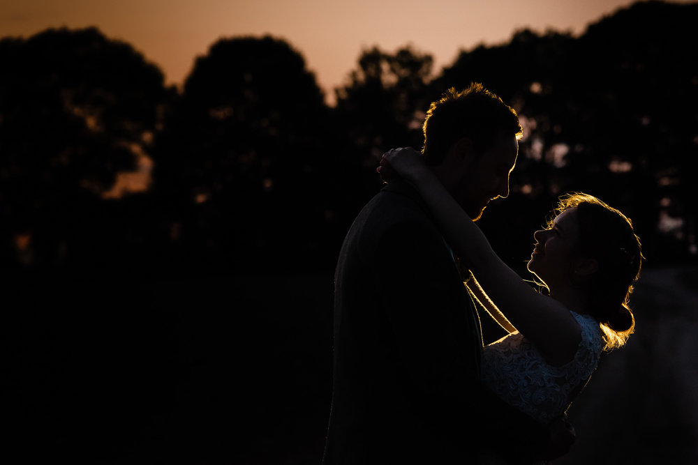 sunset night photo with bride and groom laughing with one another out side their wedding in the midlands.