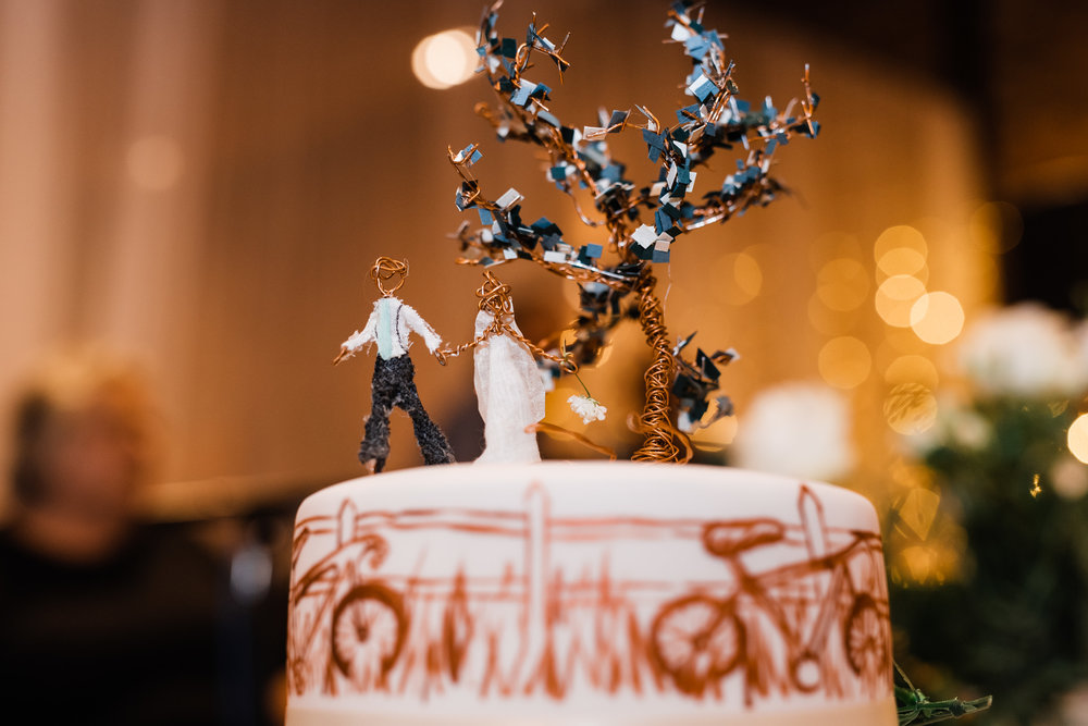 Creative wedding cake by Chitty's Cakes with illustration by Isobel H. There are beautiful bycles in the grass against a fence depicted on the top tier.