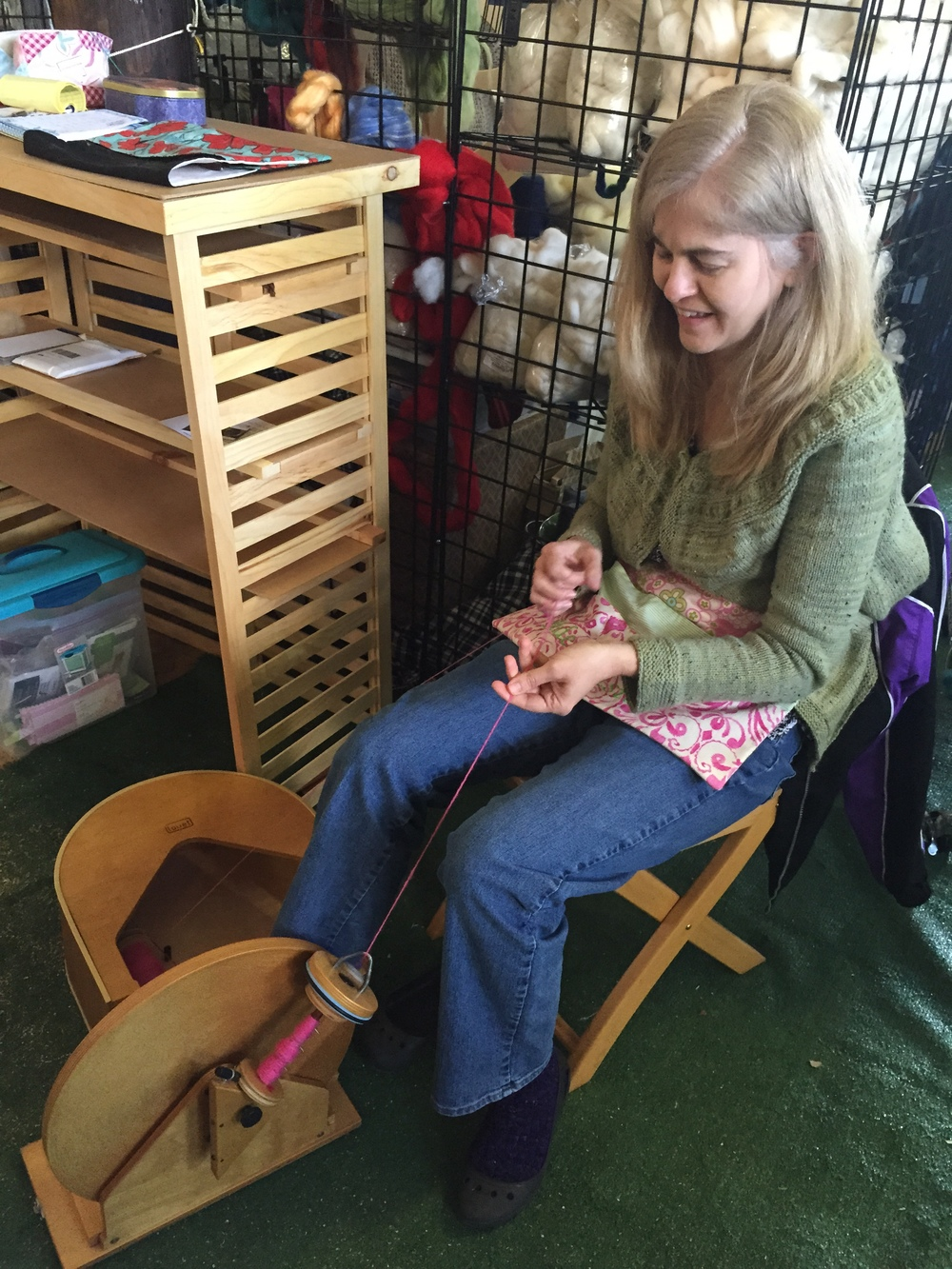 Kay from Bede Sisters passing a little time on her sweet Louet Hatbox spinning wheel.