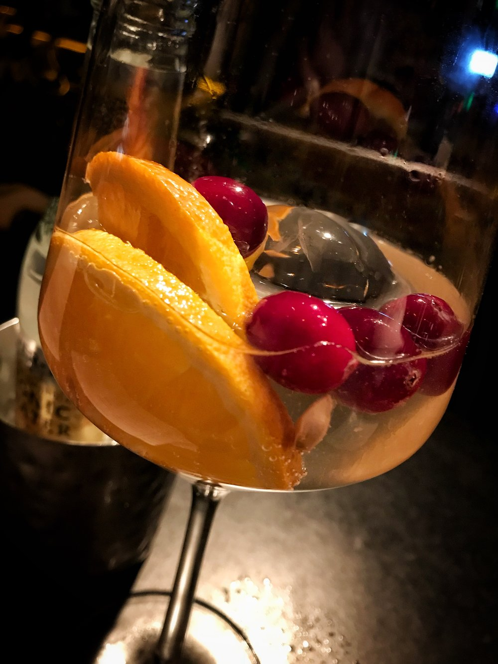 Monkey 47 gin with orange slices, cranberries, and Fever Tree Tonic Water (left).