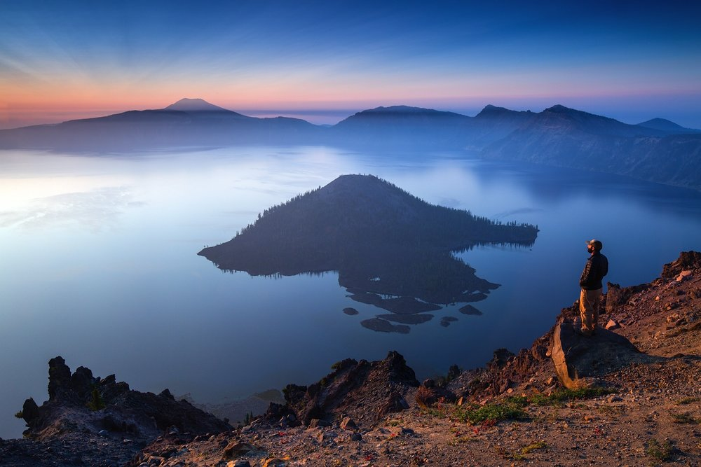 A man enjoys sunrise over Crater Lake