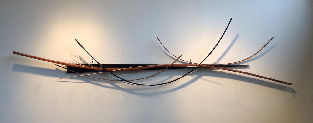 "John Schwartzkopf (BIO), Wedged Arc, 2012, paperstone, mahogany, various woods,31 1/2"" x 82"" x 5"""