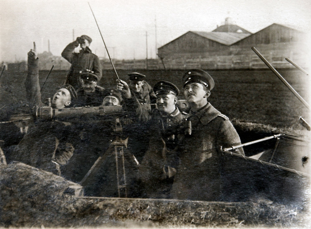 Riga, Latvia (1915): John Hasenberg (pointing with swagger stick), hamming it up with his rangefinder squad. The rangefinder (the horizontal tube on the tripod) was used to measure the distance of enemy aircraft.