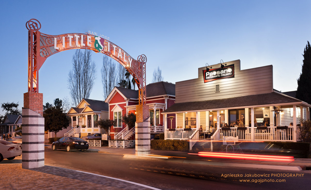 Little Italy Arch at Twilight with the view of diners on a patio of the Paesano Ristorante