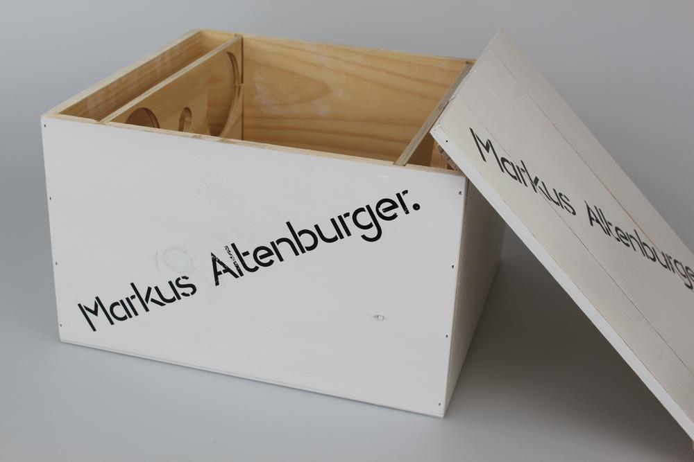 Weinkiste für sechs Flaschen aus Kiefer Massivholz, mit Flaschenhalterungen in Nut, losem Deckel. Kiste außen weiß lackiert, mit Siebdrucken auf Deckel und Seitenflächen.