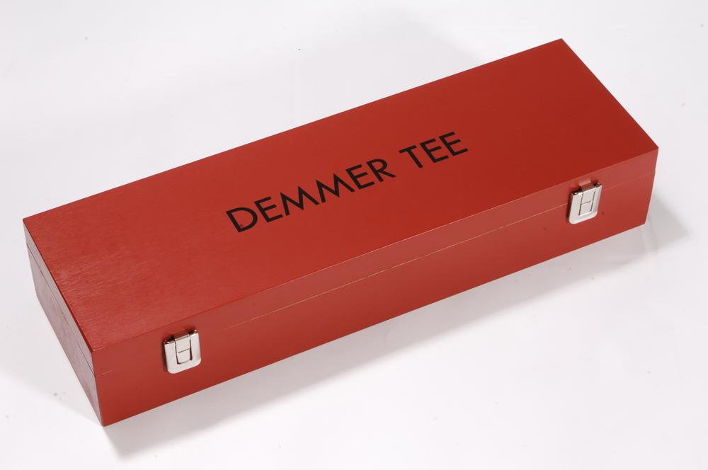 Holzverpackung für Tee aus Buchenholz, rot lackiert mit einem Siebdruck am Deckel und geschraubten Kofferbeschlägen.