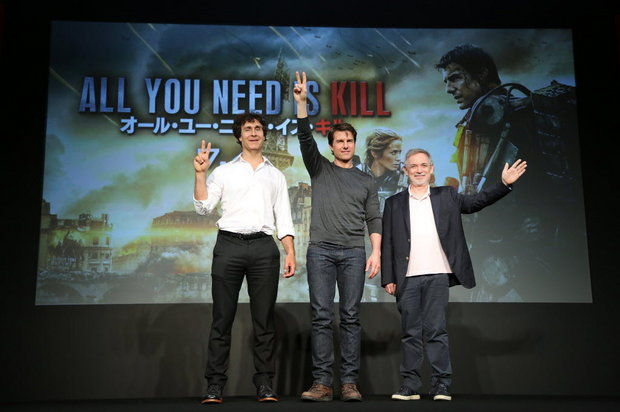 """Director Doug Liman, far left, Tom Cruise, center, and producer Erwin Stoff wave during a press conference for their latest film """" Edge of Tomorrow"""" (AP Photo)"""