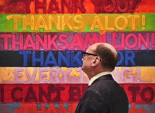 Don Christiansen, founder of CAG,  in front of a piece by Mel Bochner.