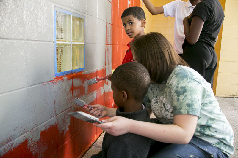 Ringling College student, Lorena, helps one of the kids paint during the mural painting event at the Roy McBean Boys and Girls Club.  © Karen Arango