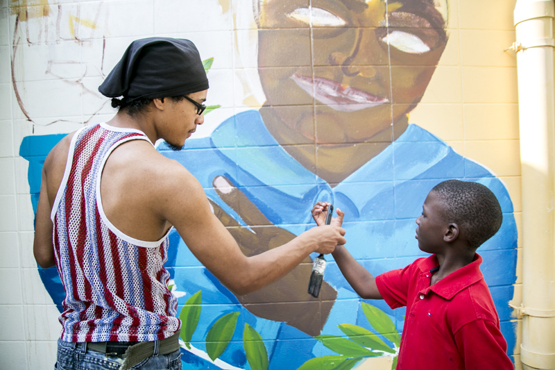 Ringling College student, Christian, helps one of the kids paint during the mural painting event at the Roy McBean Boys and Girls Club.  © Karen Arango