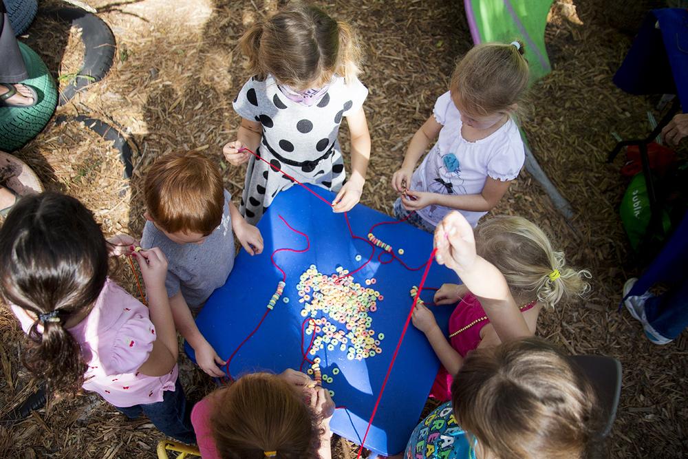 Kids make fruit loops necklaces during the  6th Annual Children's Reading and Art Day Festival  at the Sarasota Children's Garden.  © Karen Arango