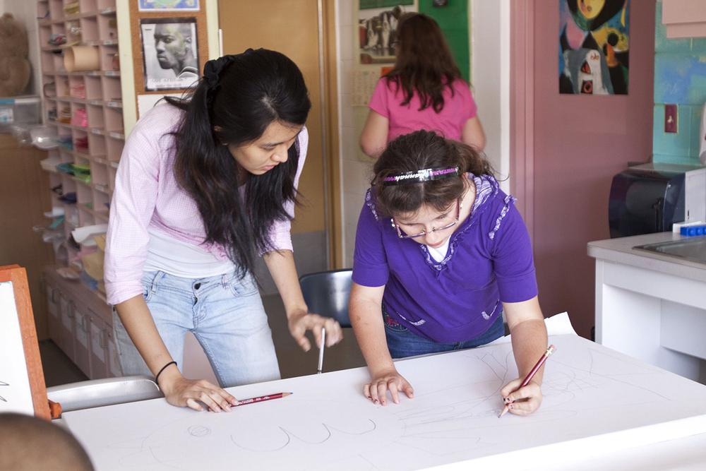 Ringling College undergraduate helps her student during the YEA Arts Program.  © Karen Arango