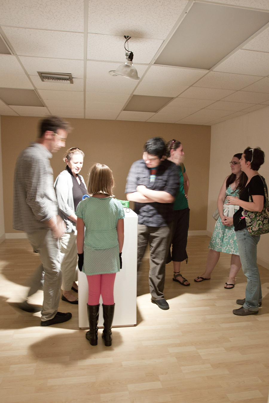 Adults and kids carefully observe one of the art works during the  s/ART/q Invitational Exhibition.   © Karen Arango