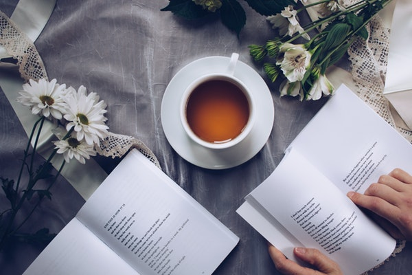 reading with a daisy, tea and book.jpeg