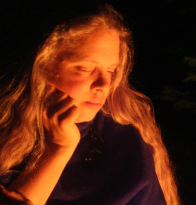 Image of Arie Farnam with long light-colored hair unbound and eyes closed as she looks into a fire at night