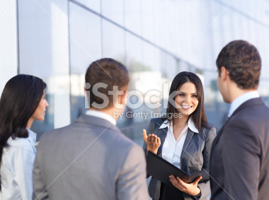 stock-photo-18307915-young-business-woman-talking-with-colleagues.jpg