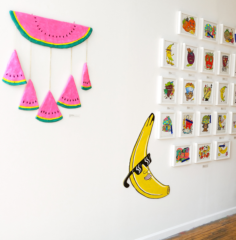 My watermelon danglers and Rob's work. His illustrations were framed & hung in grids, with a few cutouts he made to mix it up.