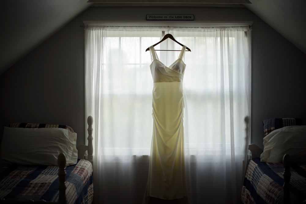 Hanging wedding dress in window at Rye Beach in New Hampshire