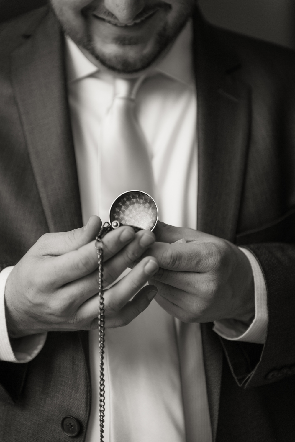 Groom getting ready with gift from bride