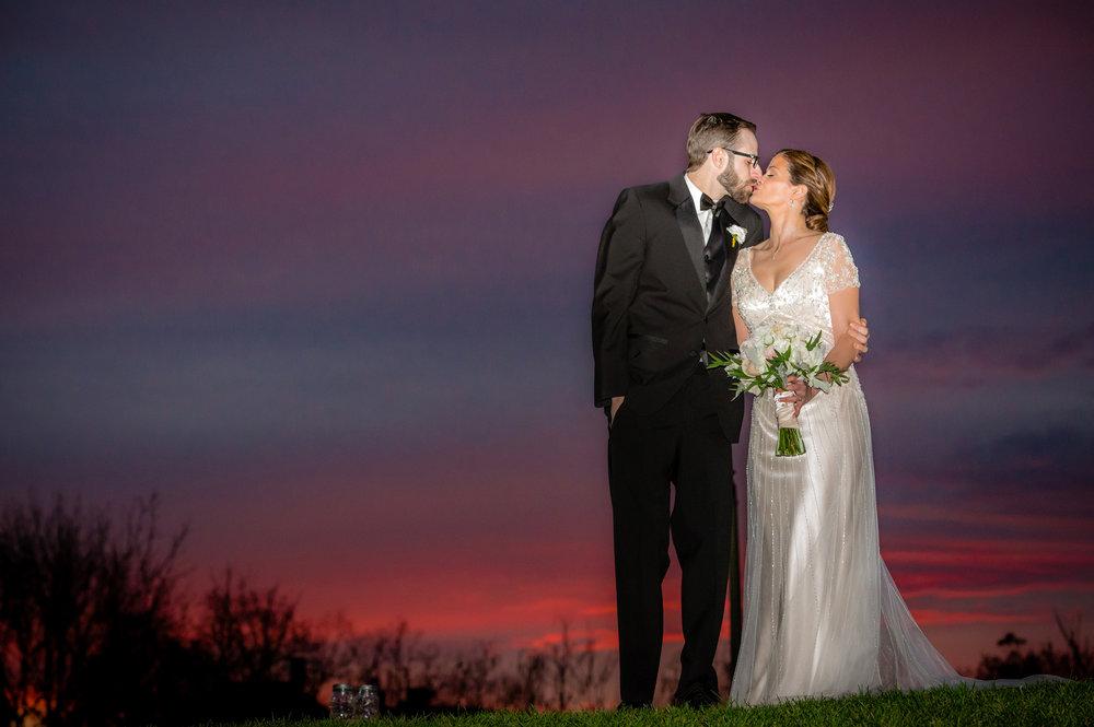 bride and groom share a kiss at sunset at Barn at Gibbet Hill, Groton, MA