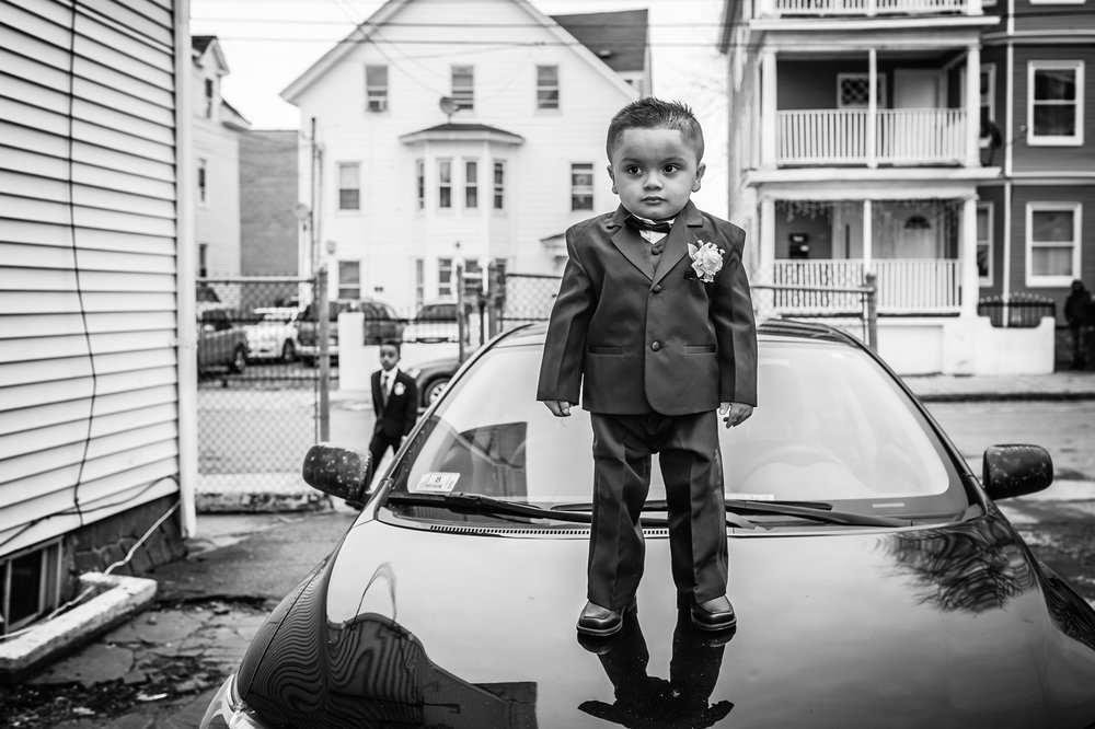 Little ringbearer standing on car in Lawrence, MA, photographed by Mike Sears Photography