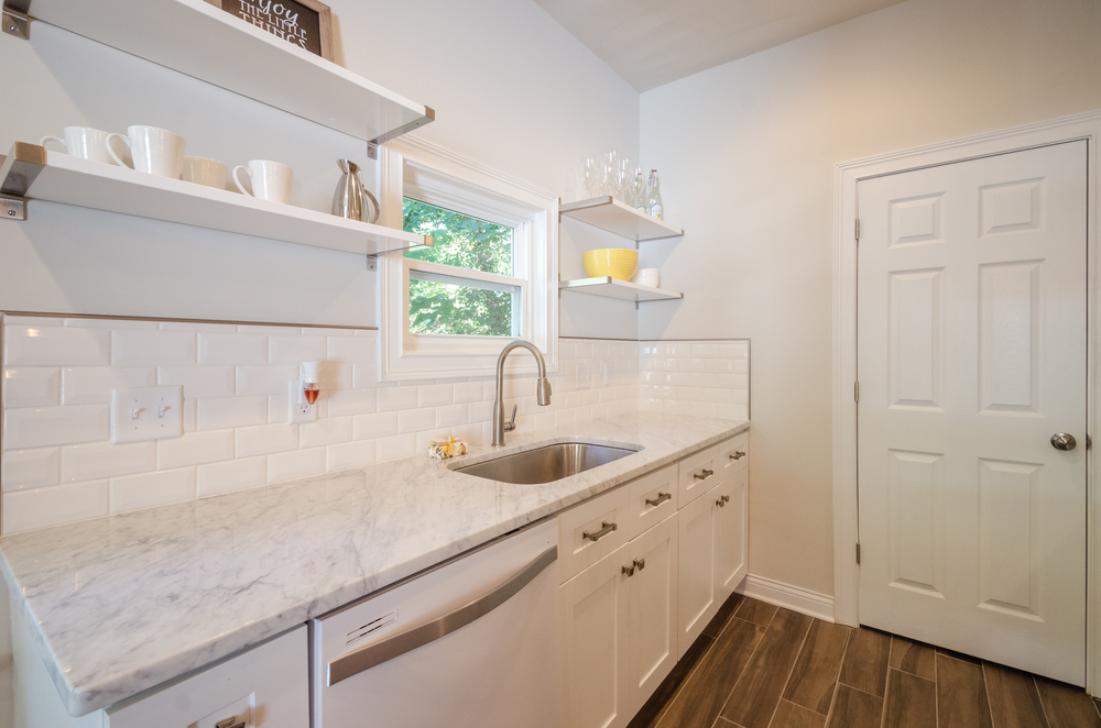 White Shaker Cabinet Kitchen with Carrara Marble Counters and beveled subway tile backsplash