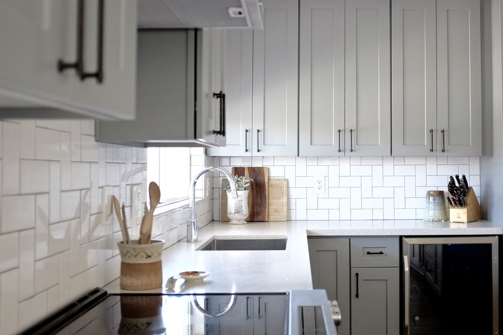 Gray Kitchen with Subway Herringbone Tile and Quartz counter tops