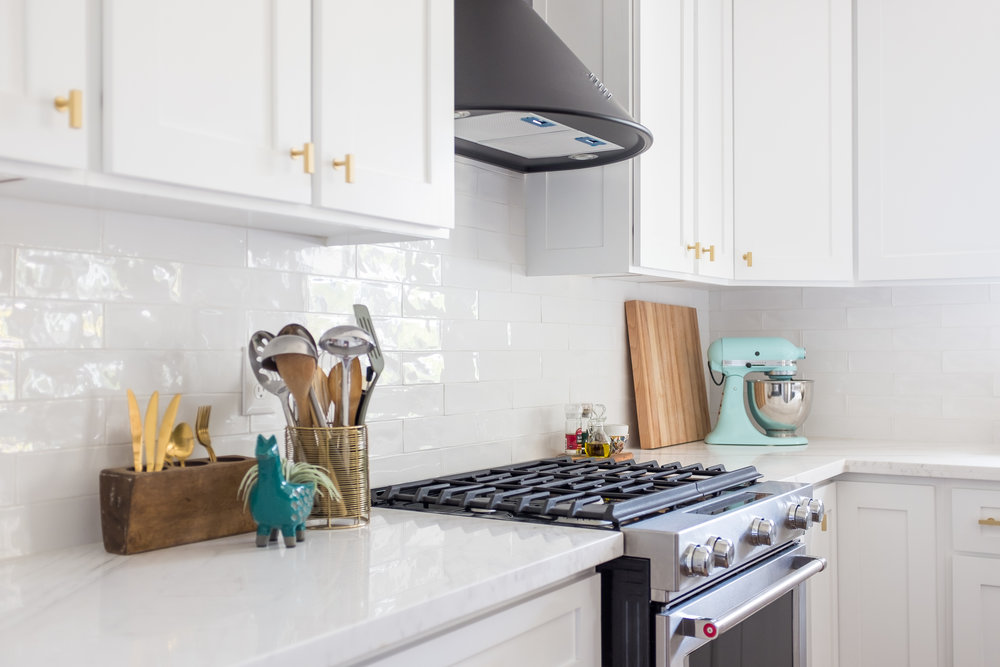 White kitchen with black retro hood, marble counters and white subway backsplash. Retro accents