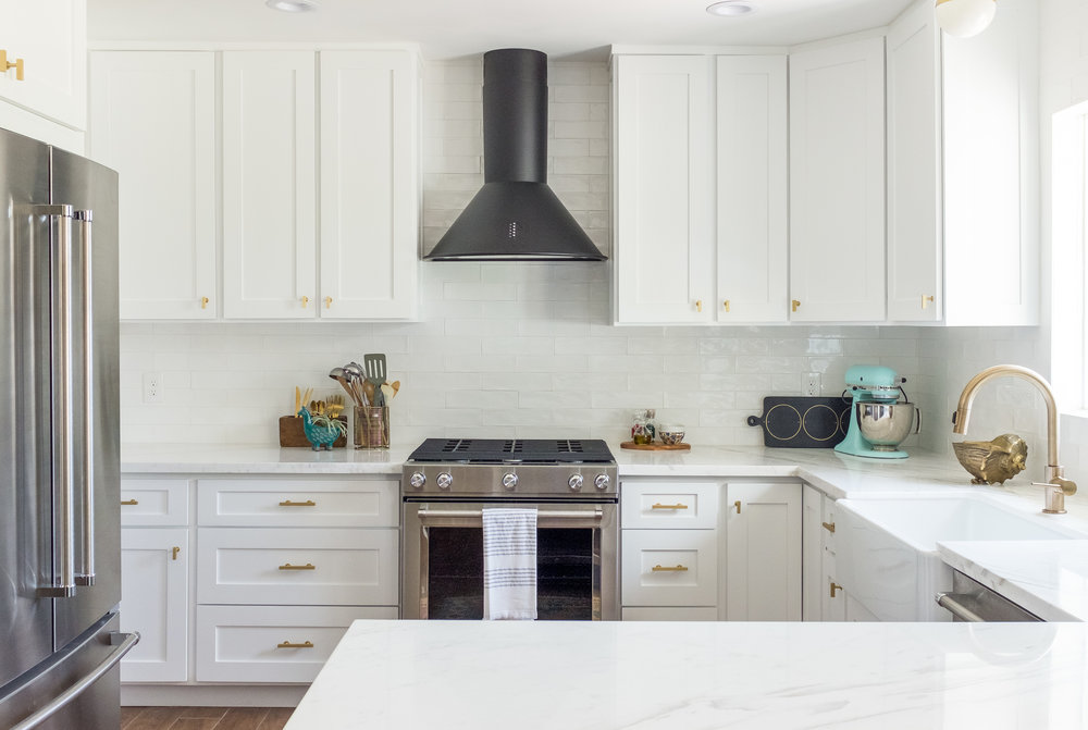 White Shaker Kitchen with long subway tiles, black retro hood and gold brass pulls