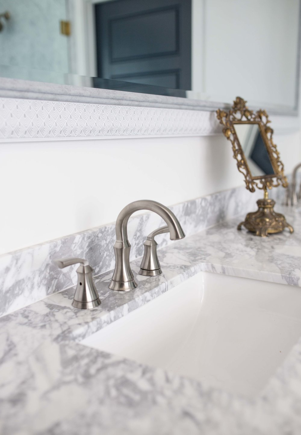Marble counters with nickel faucets and gold make up mirror