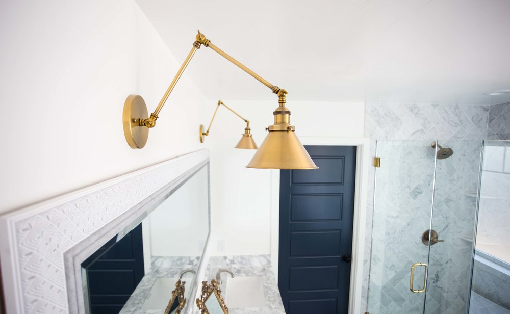 Brass sconce lighting over marble vanity in master bathroom