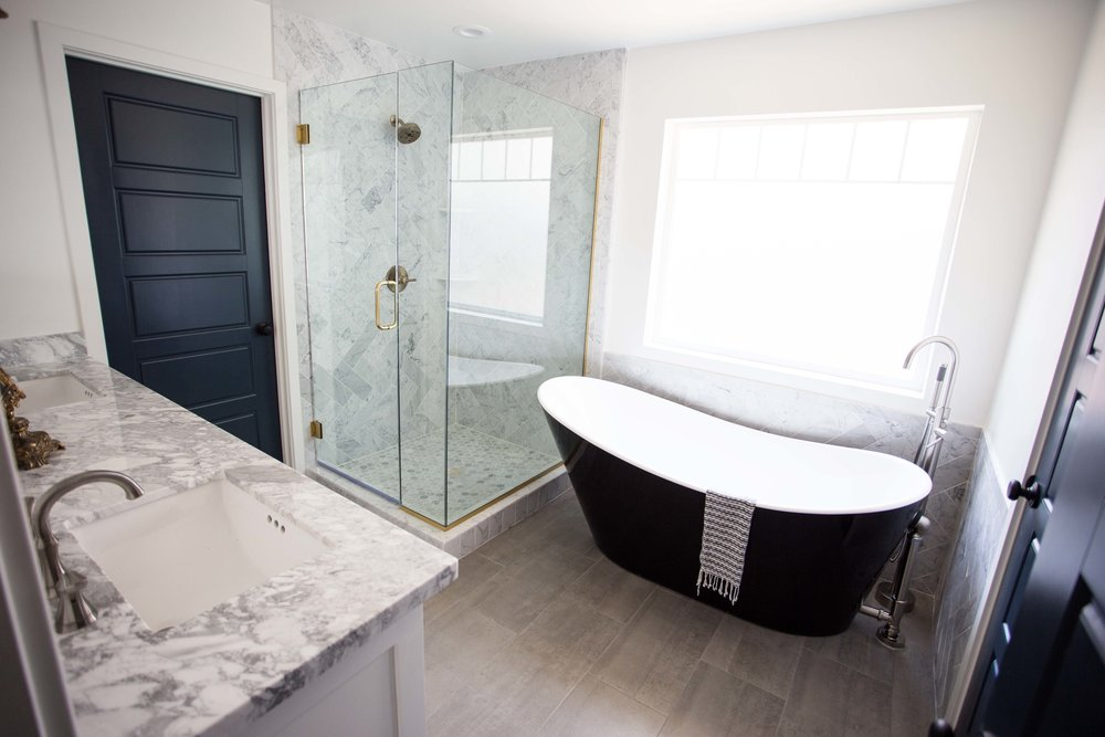 Master bathroom with marble herringbone shower and wall tile, black soaking tub and brass and nickel fixture finishes