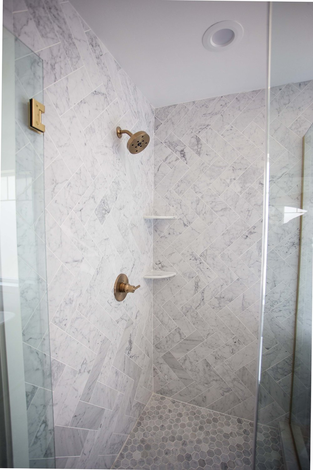 Herringbone marble and brass fixtures and shower door hardware