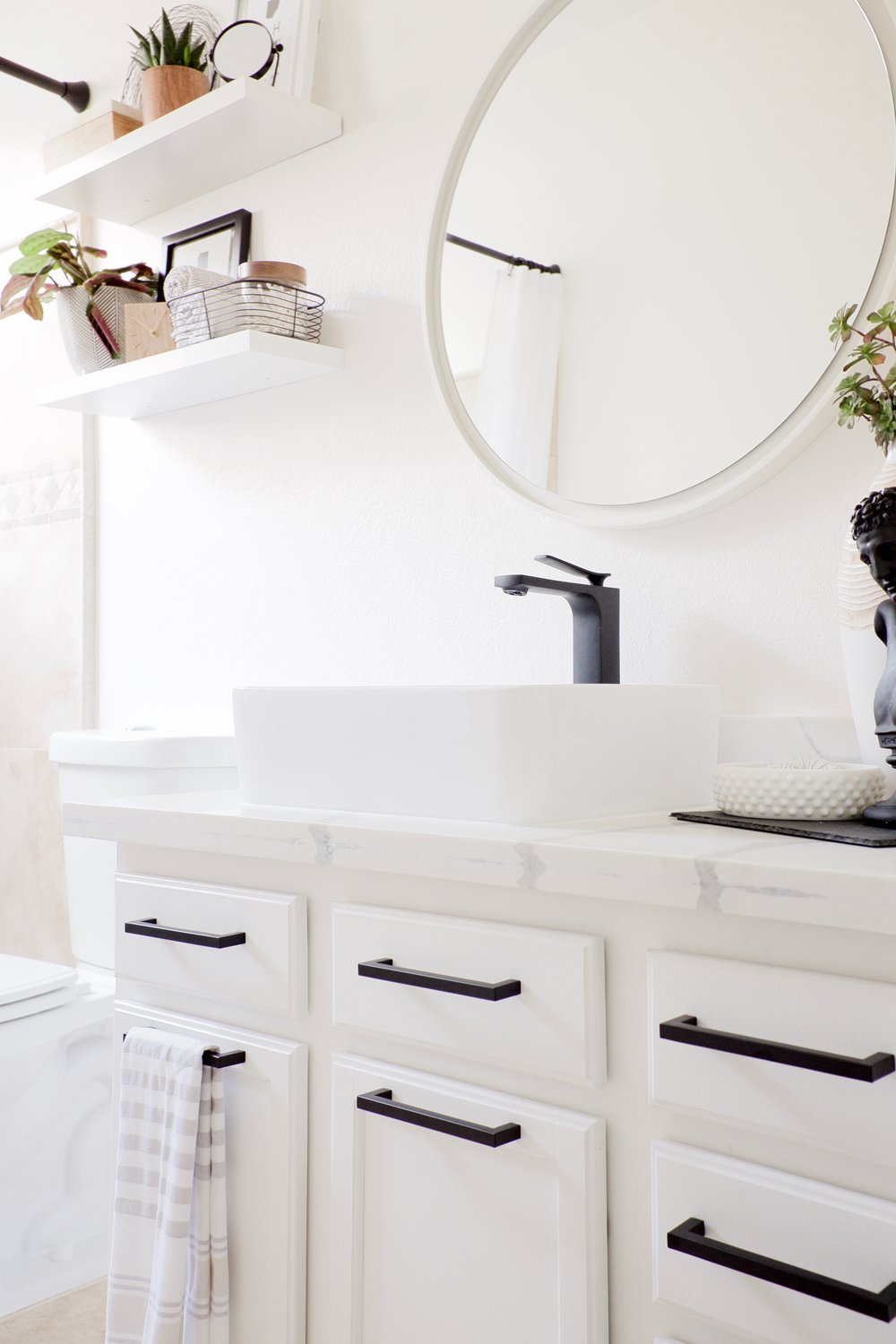 White cabinet with white round mirror and quartz counter, black fixtures