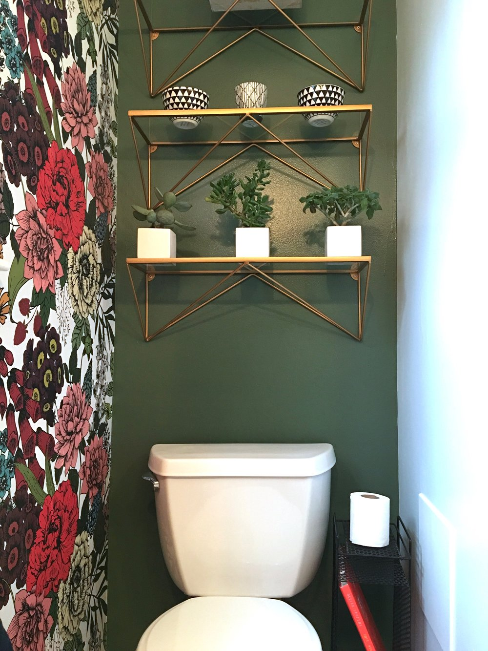 Retro Bathroom with Green Toilet wall, gold brass floating shelves and old phone stand for toilet paper
