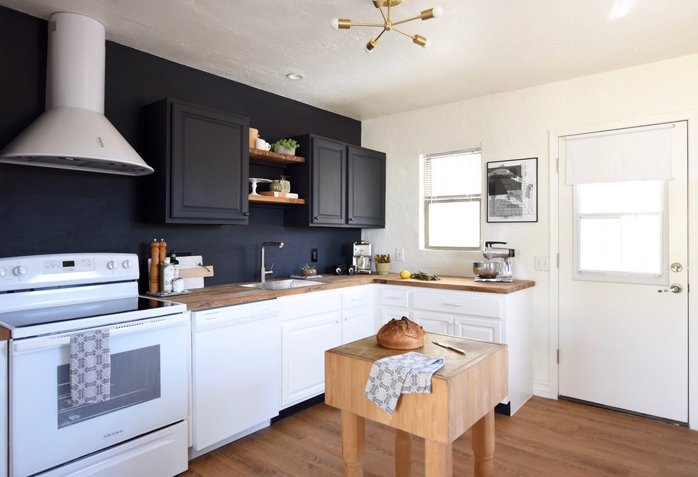 Black upper cabinets and white appliances with vinyl plank flooring over tile, butcher block counters
