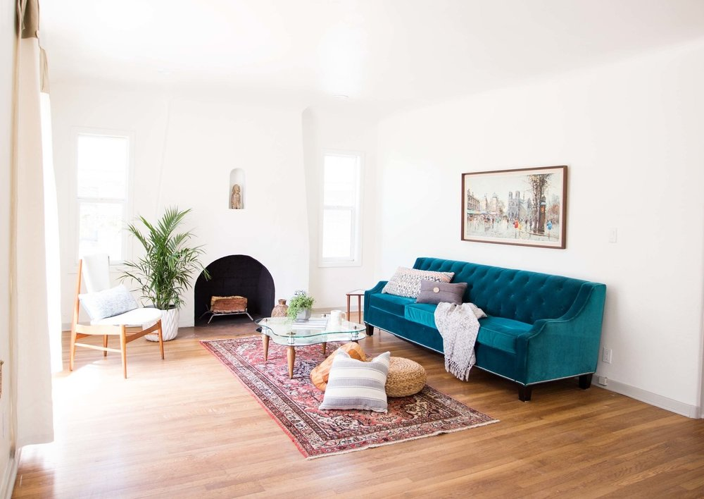 Styled turquoise sofa, hardwood floors, spanish style