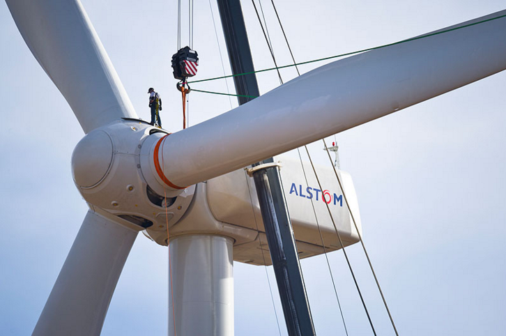 A worker from Michels Wind Energy prepares to release a harness after the third and final blade was attached to an Alstom Eco 100 wind turbine.      Credit : Dennis Schroeder.  Via : NREL