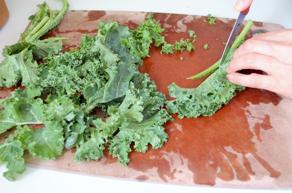 Fold the leaves in two after washing, and cut out the rib of each leaf. Then rip or chop into smallish pieces.