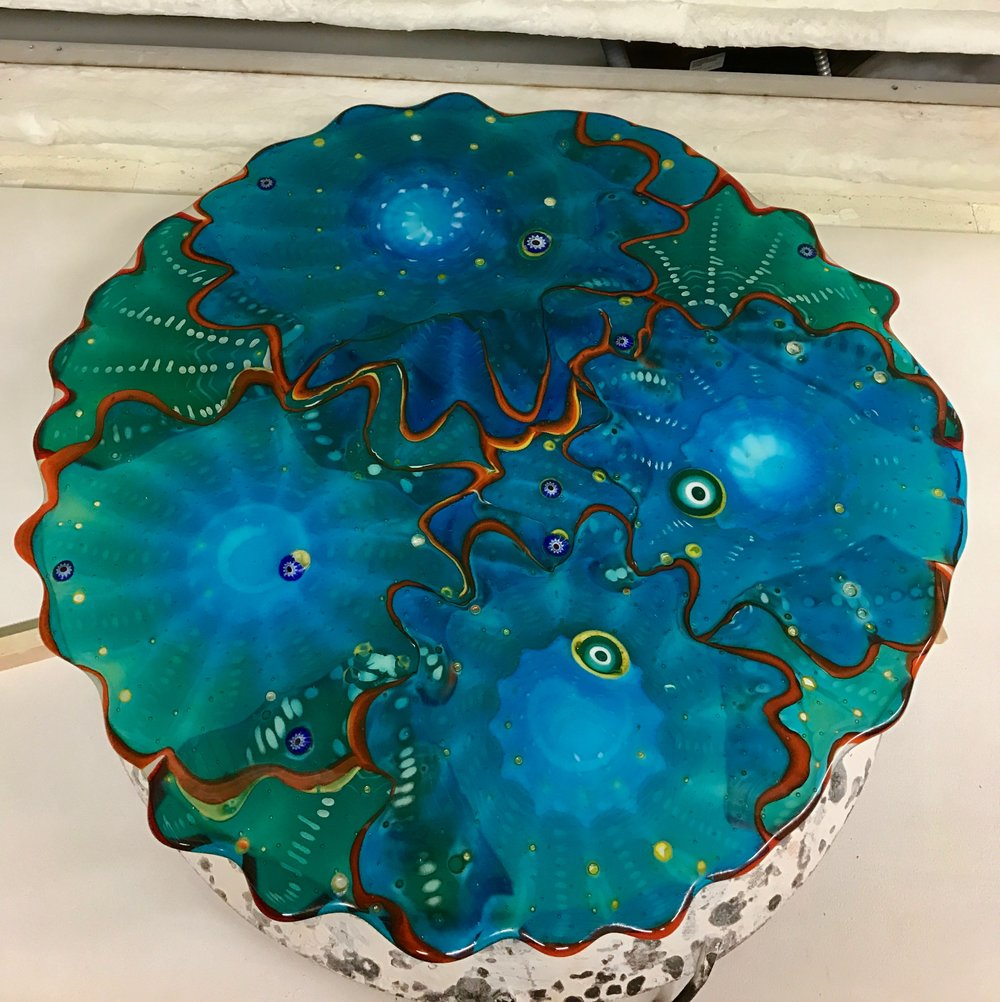 "This 24 "" fused Platter of Blown Rondels is now in the kiln to be slumped into a dome for an up light.   stay tuned.  strini"