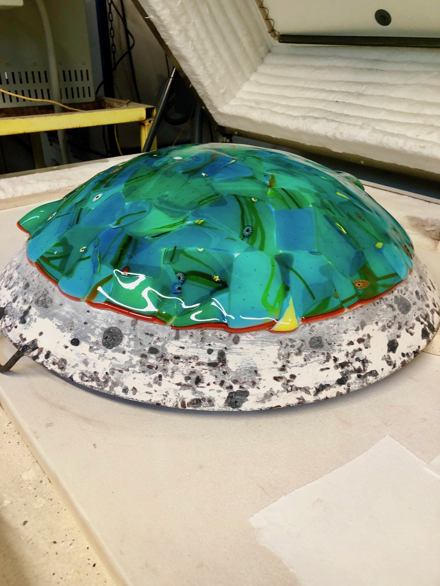 "Taken up to around 1200 degrees F. the glass lays down,  ""slumps"" into place and now is the dome when its hung up. strini art glass. 2108"