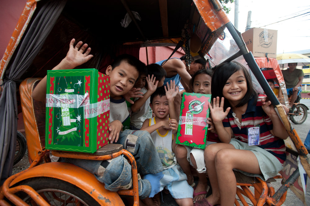 WHY WE PACK SHOEBOXES From children to seniors, people pack shoeboxes each year to bless children in need around the world. Parents often use the project to teach their kids about giving. Long before shoeboxes arrive in more than 100 countries, volunteer National Leadership Teams train pastors and community leaders who want to share the message of the Gospel and bless children. These leaders learn how to host child-friendly outreach events, and how to implement The Greatest Journey follow-up discipleship program. As a result of what they learn in The Greatest Journey, boys and girls grow in Christ and share with friends and family. This often brings parents, siblings, and friends to accept Christ and become active members in the local church. Families are reached, churches grow, new churches are started, and communities are transformed.  It all starts with you!  Join what God's doing and pack a shoebox. Download a shopping list here.